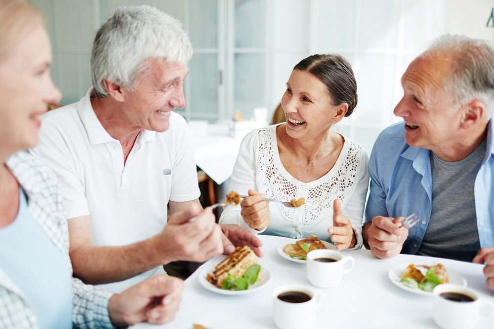 Cheerful senior friends having tasty dessert and talking in cafe