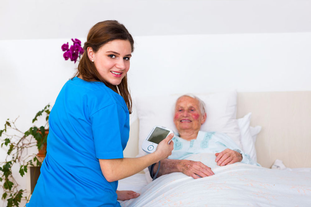 Happy nurse smiling to the camera while measuring senior woman's blood pressure in nursing home.