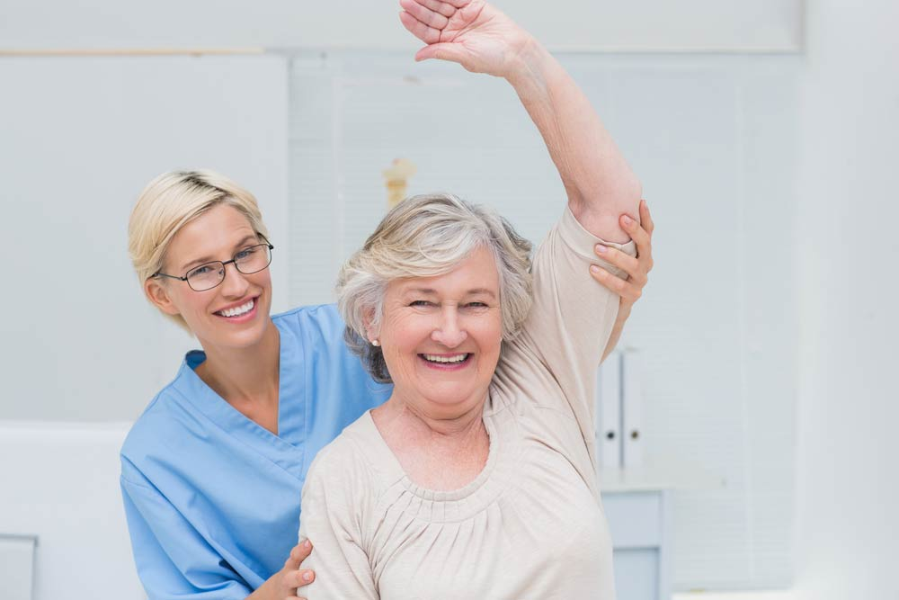 Portrait of happy senior patient being assisted by nurse in raising arm at clinic
