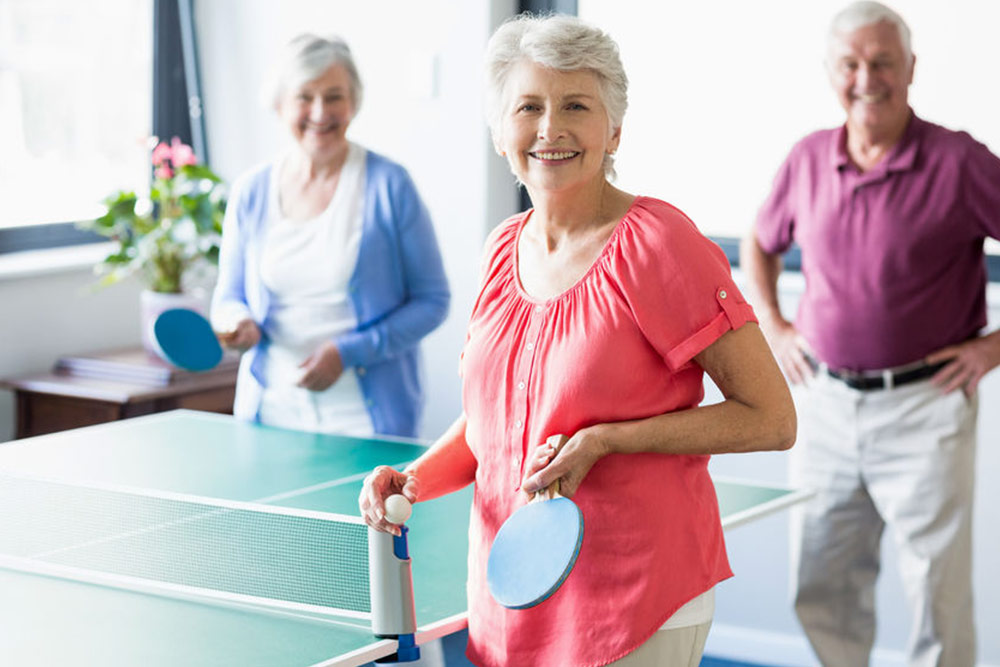 Seniors playing ping-pong in a retirement home