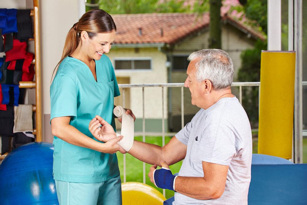 Nurse changing bandage on wrist of senior man at physiotherapy
