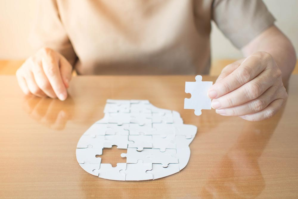 Elderly woman hands holding missing white jigsaw puzzle piece down into the place as a human head brain shape. Creative idea for memory loss, dementia, Alzheimer's disease and mental health concept
